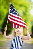 Urocza małej dziewczynki mienia flaga amerykańska outdoors na pięknym letnim dniu Zdjęcia Royalty Free