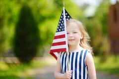 Urocza małej dziewczynki mienia flaga amerykańska outdoors na pięknym letnim dniu Obrazy Royalty Free