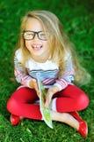 Urocza małej dziewczynki mienia książka i śmiać się Zdjęcia Stock