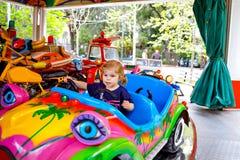 Urocza ma?a berbe? dziewczyny jazda na ?miesznym samochodzie na ronda carousel w parku rozrywkim Szcz??liwy zdrowy dziecka dzieck obraz stock