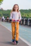 Urocza mała dziewczynka jedzie jej hulajnoga w lato parku Zdjęcia Royalty Free