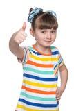Urocza mała dziewczynka trzyma jej aprobaty Obrazy Royalty Free