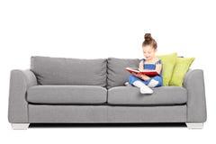 Urocza mała dziewczynka czyta książkę na kanapie Obraz Royalty Free
