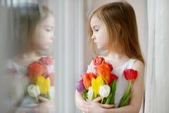 Urocza mała dziewczynka z tulipanami okno Obraz Royalty Free