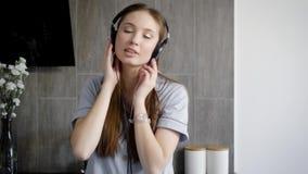 Urocza nastoletnia dziewczyna jest słuchającym muzyką w hełmofonach salowych zbiory wideo