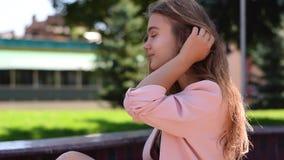 Urocza nastoletnia dziewczyna z prosto tęsk blondynka włosy obsiadanie w parkland zbiory