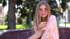 Urocza nastoletnia dziewczyna z prosto tęsk blondynka włosy obsiadanie w parkland zbiory wideo