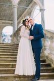 Urocza nowożeńcy para - przygotowywa trzymać jego ładnej panny młodej podczas gdy oba stoją na antyka kamienia schodkach folował  Obrazy Royalty Free