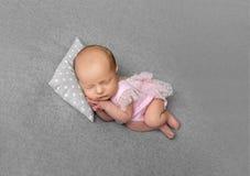 Urocza nowonarodzona dziewczyna w różowy drees spać obraz royalty free