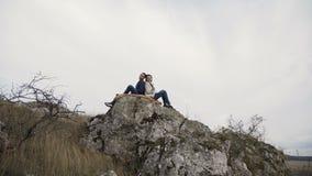 Urocza para odpoczywa w uściskach na wierzchołku skała w wietrznym dniu 4K zdjęcie wideo