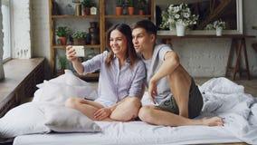 Urocza potomstwo para robi wideo wezwaniu z smartphone, młodzi ludzie siedzący dalej są opowiadający i gestykulujący podczas gdy zbiory