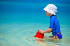 Urocza szczęśliwa mała dziewczynka zabawę przy płycizną Fotografia Stock