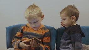 Urocze berbeć chłopiec siedzi na krześle i używa smartphone 4K zbiory