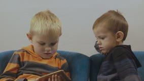 Urocze berbeć chłopiec siedzi na krześle i używa smartphone 4K zbiory wideo
