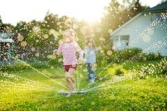 Urocze małe dziewczynki bawić się z kropidłem w podwórku na pogodnym letnim dniu Śliczni dzieci ma zabawę z wodą outdoors zdjęcia stock
