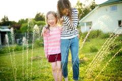 Urocze małe dziewczynki bawić się z kropidłem w podwórku na pogodnym letnim dniu Śliczni dzieci ma zabawę z wodą outdoors zdjęcie stock