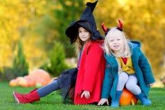 Urocze małe dziewczynki jest ubranym Halloween kostium ma zabawę na dyniowej łacie Zdjęcie Stock