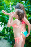 Urocze małe dziewczynki pod plażową prysznic na tropikalnej plaży obrazy stock