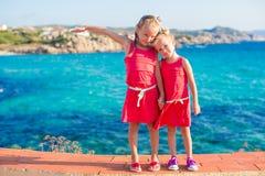 Urocze małe dziewczynki przy tropikalną plażą podczas wakacje Obrazy Royalty Free