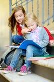 Urocze małe uczennicy studiuje outdoors na jaskrawym jesień dniu Młodzi ucznie robi ich pracie domowej Edukacja dla małych dzieci Zdjęcia Royalty Free