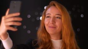 Uroczej rudzielec caucasian kobieta trzyma, ma wideo wezwanie, relaksuje jej telefon w ręce, pozycję i opowiadać indoors