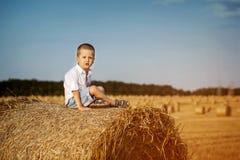 Uroczy śliczny chłopiec obsiadanie na haystack w banatce Zdjęcia Stock