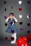 Uroczy śmieszny biały Kaukaski mała dziewczynka berbeć w studiu z czerwień balonów sercami na popielatym tle robi twarzom ma zaba Zdjęcia Royalty Free
