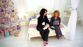 Uroczy żeńscy przyjaciele zabawę i używają pastylkę, siedzi na łóżku w jaskrawej sypialni z świąteczną choinką w wieczór zbiory