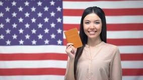 Uroczy żeński pokazuje paszport przeciw usa flagi tłu, obywatelstwo zdjęcie wideo