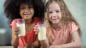 Uroczy afrykanin i Kaukaskie dziewczyny trzyma szkła mleko, zdrowy łasowanie fotografia royalty free