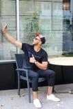 Uroczy arabski facet robi selfie i siedzi w krześle, podnoszący rękę, s Zdjęcia Royalty Free
