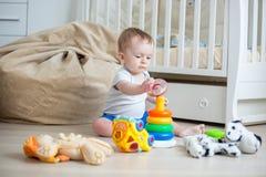 Uroczy berbeć chłopiec obsiadanie na podłoga i budynku kolorowej zabawce góruje Zdjęcie Stock