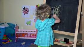 Uroczy berbeć dziewczyny rysunek na chalkboard w domu zdjęcie wideo