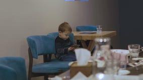 Uroczy berbeci przyjaciele siedzi na krześle i bawić się smartphone 4K zbiory
