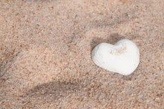 Uroczy biały skorupy serce na piasku Zdjęcie Royalty Free