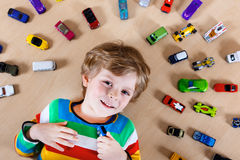 Uroczy blondyny żartują chłopiec bawić się z udziałami zabawkarscy samochody salowi obrazy stock