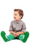 Uroczy chłopiec obsiadanie na podłoga i patrzeć somethin Fotografia Royalty Free