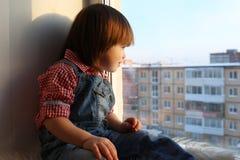 Uroczy chłopiec spojrzenia z okno w wintertime (2 roku) Obraz Stock