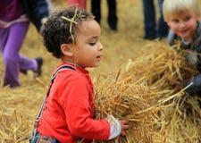 Uroczy dzieci ma zabawę Bunratty kasztel, Irlandia, 2014 podczas gdy bawić się w haystacks