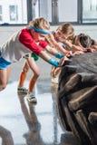 Uroczy dzieciaki w sportswear szkoleniu z oponą przy sprawności fizycznej studiiem zdjęcia stock