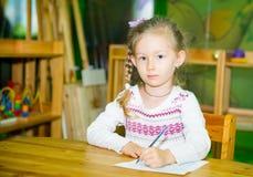 Uroczy dziecko dziewczyny rysunek z kolorowymi ołówkami w pepiniera pokoju Dzieciak w dziecinu w Montessori preschool klasie Zdjęcia Royalty Free