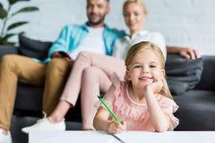 uroczy dziecko rysunek z ołówkowym i ono uśmiecha się przy kamerą podczas gdy rodzice zdjęcia royalty free