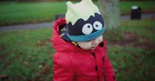 Uroczy dziecko w czerwonej kurtce i śmieszny kapeluszowy odprowadzenie w zieleń parku Czerwona epopeja 4k swobodny ruch zbiory
