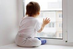 Uroczy dziecko wiek 1 roku spojrzenia z okno w zimie Obraz Royalty Free