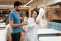 Uroczy dziewczyna konsultant demonstruje ortopedyczną materac ufny mężczyzna w meblarskim sklepie obraz royalty free