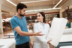Uroczy dziewczyna konsultant demonstruje ortopedyczną poduszkę ufny mężczyzna w meblarskim sklepie zdjęcie royalty free