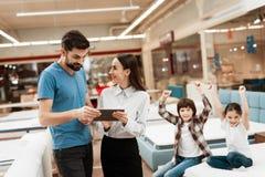 Uroczy dziewczyna konsultant z ufnym mężczyzna robi out zakupowi materac w sklepie zdjęcie royalty free