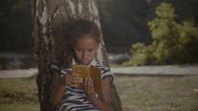 Uroczy dziewczyna networking na telefonie komórkowym pod drzewem zdjęcie wideo