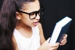 Uroczy dziewczyny studiowanie z eyeglasses i książką w ręce Zdjęcie Stock