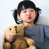 Uroczy i niewinnie azjatykci dzieciak bawić się z misiem pluszowym szczęśliwie Obrazy Royalty Free